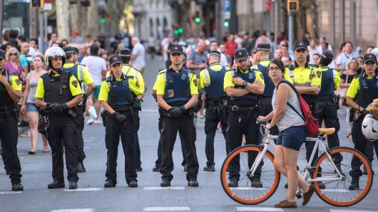 BARCELONA, SPAIN - AUGUST 18: A cyclist pushes her bike past a line of police officers on Las Ramblas near the scene of yesterday's terrorist attack, on August 18, 2017 in Barcelona, Spain. Fourteen people were killed and dozens injured when a van hit crowds in the Las Ramblas area of Barcelona on Thursday. Spanish police have also killed five suspected terrorists in the town of Cambrils to stop a second terrorist attack. (Photo by Carl Court/Getty Images)
