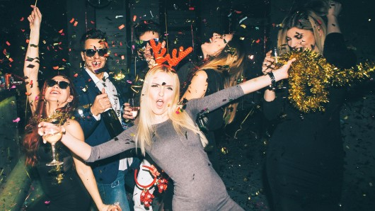 Group of friends having fun for new year's eve in a club. Drinking and dancing together